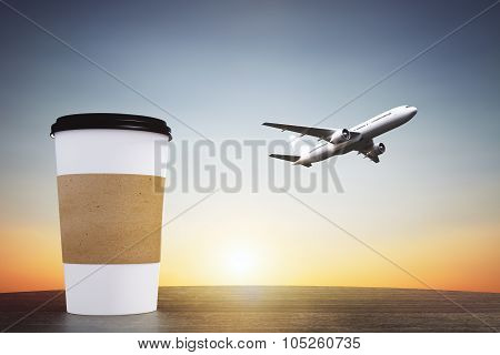 Blank Paper Cup Of Coffee On A Wooden Table And Flying Away Aircraft, Travel Concept