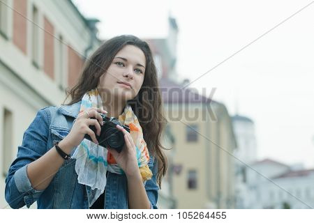 Travel portrait of taking pictures brunette girl with vintage SLR camera