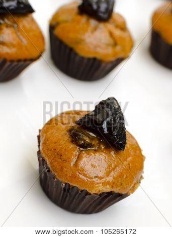 close up shot prune muffins cupcake on white background