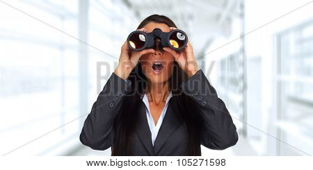 Business woman with binoculars over office background.