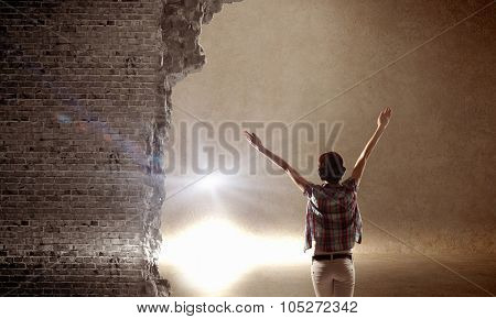 Rear view of woman with hands up entering crack in wall