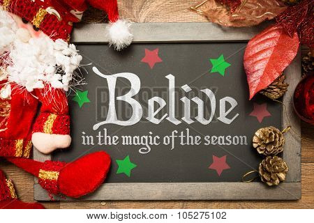 Blackboard with the text: Believe in the Magic of the Season in a christmas conceptual image