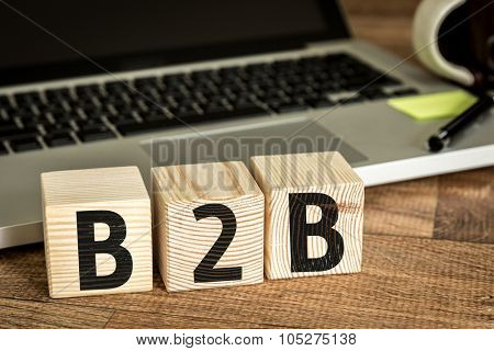 B2B written on a wooden cube in front of a laptop