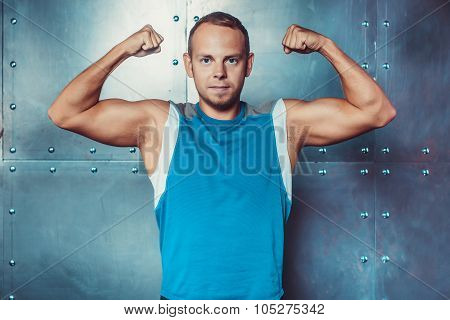 Athlete, sportsman muscular man shows his muscles and looking at the camera