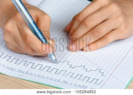 Hands Of Child Writing In Copy-book