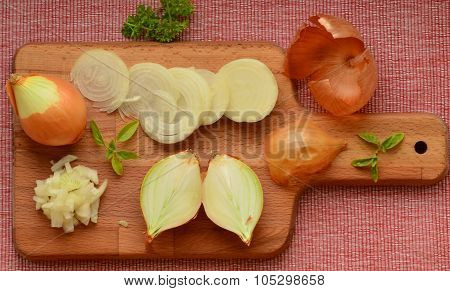 Chopped onion and slices of onion on chopping board