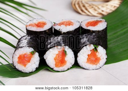 sushi roll salmon chives mini kappa maki in the still life on a tropical leaves