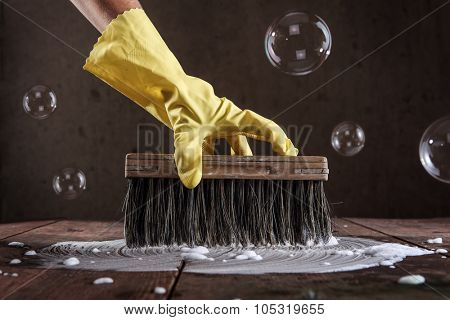 Hand in rubber glove scrubbing a wooden floor with an old brush