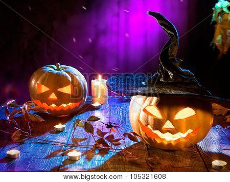 Halloween pumpkin head jack lantern with burning candles. Halloween holidays art design, celebration. Carved Halloween Pumpkins with burning candles in scary deep night forest