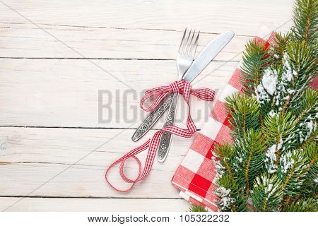 Silverware and christmas tree. View from above over white wooden table background with copy space