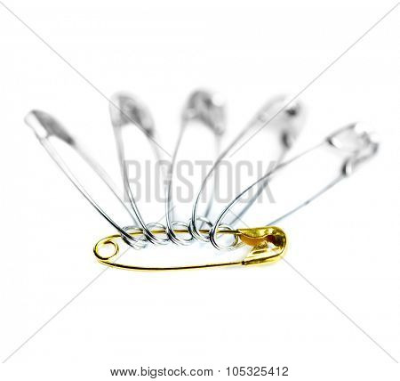 Safety pin one golden color and many other. Leadership concept