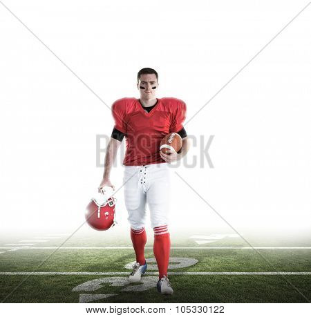 Portrait of american football player walking and holding football and helmet against american football pitch