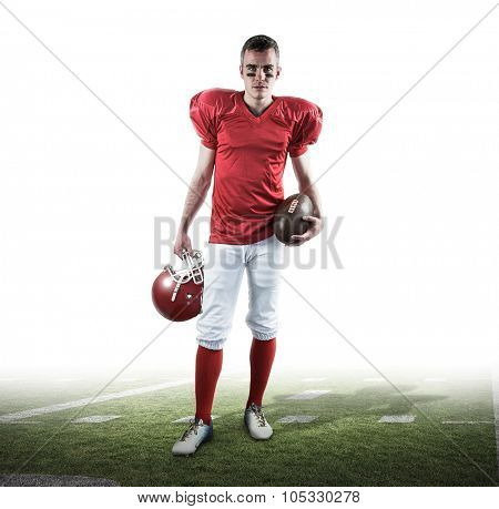 A serious american football player taking his helmet on her hand looking at camera against american football pitch