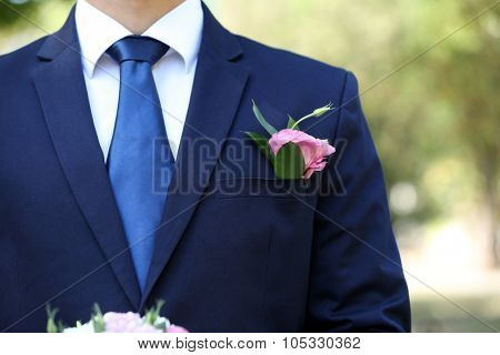 Groom with boutonniere outdoors