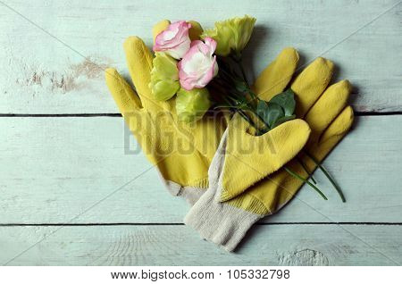 Pretty composition of blossom and gardener's gloves on light-blue wooden background