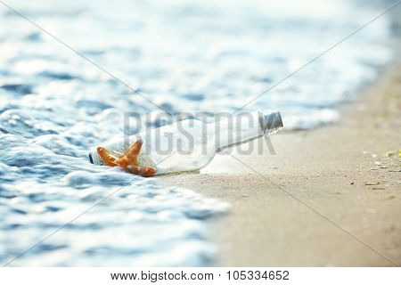 Bottle with starfish on sandy beach