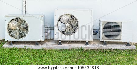 Three Old Air Conditioner Beside Home