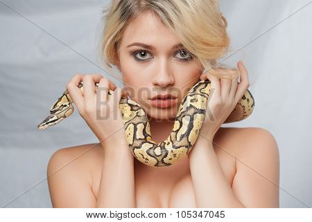 Beautiful girl  holding a python, which wraps around her face