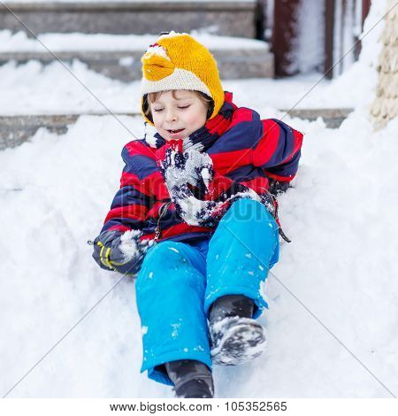 Kid Boy In Colorful Clothes Having Fun With Riding On Snow, Outdoors