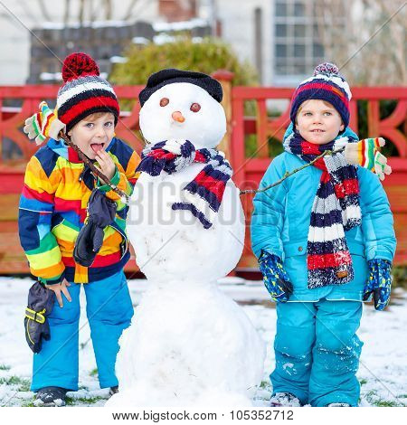 Two Little Siblings Boys Making A Snowman, Playing And Having Fu