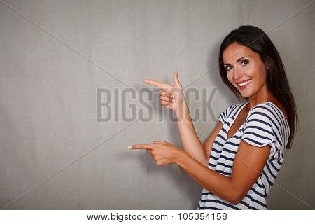 Happy Young Woman Pointing While Standing