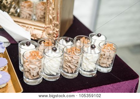 Wedding decoration with pastel colored sweets in small glasses. Elegant and luxurious event