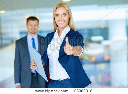 Successful young businesswoman showing ok
