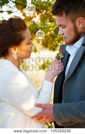 Young Wife Pinning Buttonhole Flowers To Groom's Coat