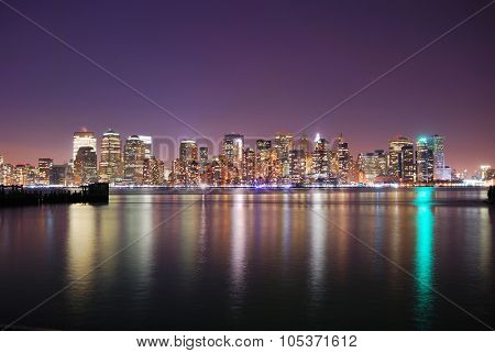 New York City Manhattan skyline night panorama over Hudson River with reflection.