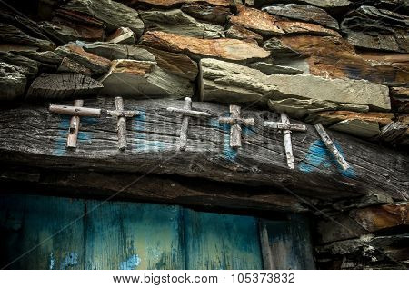 Group of wooden crosses over rural house door to protect harvest