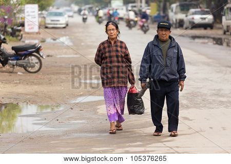 MANDALAY,MYANMAR,JANUARY 17, 2015: An elderly couple is walking in a street, going to the market in Mandalay, Myanmar (Burma).