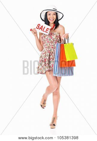 Young happy smiling woman holding a signboard announcing a Sale and bags, isolated on white background
