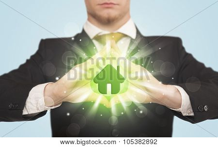 Hands creating a form with shining green house in the center