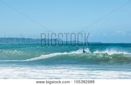 Kite surfer athlete on big sea wave. Extreme sports