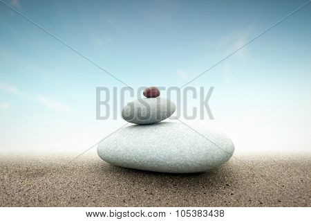 Spiritual concept background of stones tower pyramid on sand with light behind