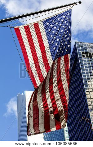 Bright American Flag And The Skyscrappers In A Sunny Weather