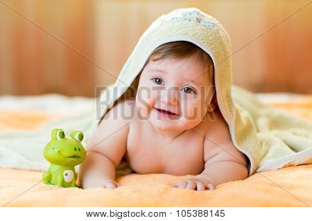 Cheerful baby child under a hooded towel after bath