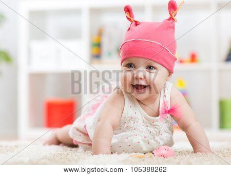 Smiling baby child crawling on nursery floor
