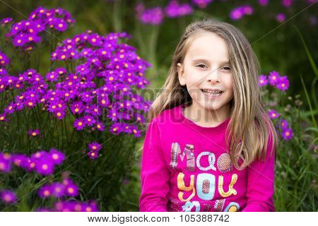 Pretty smiling girl is field of flowers