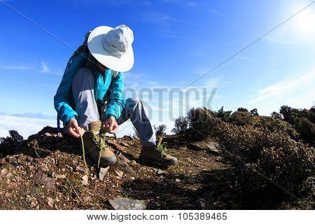 Young Woman Hiker Tying Shoelace On Beautiful Mountain Peak