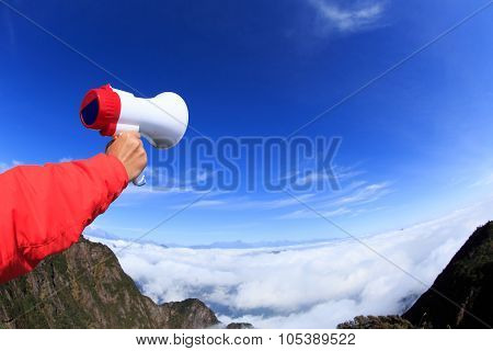 People Hand Hold Loudspeaker To Blue Sky On Mountain Peak