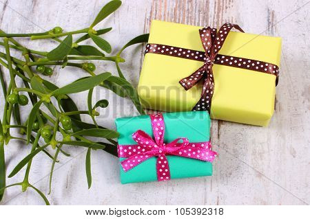 Wrapped Colorful Gifts For Christmas And Mistletoe On Old Wooden Background