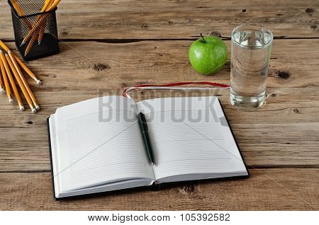 Open Diary With Blank Pages With A Glass Of Water