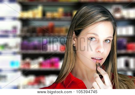 Blonde woman applying lipstick in a perfumery