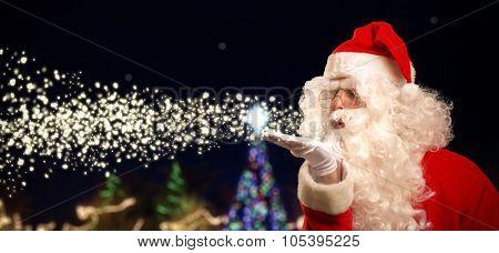Portrait of Santa Claus blowing magic snow