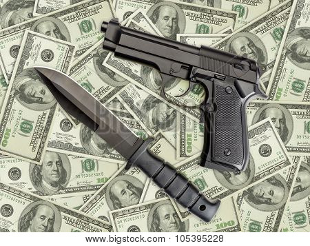 Knife and pistol placed on pile of american one hundred dollar bills