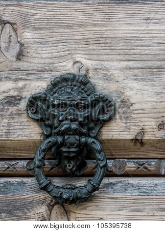 Closeup of old metal knocker attached to wooden doors
