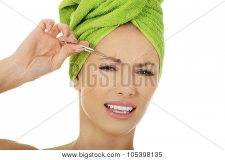 Beautiful caucasian woman plucking her eyebrow.