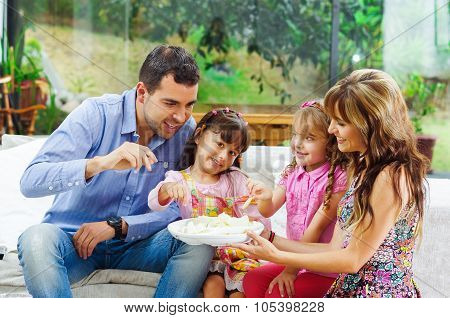 Hispanic parents with two daughters eating from a tray of potato chips sitting in sofa while smiling
