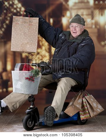 A senior Christmas shopper delighted with his purchase as he drives his scooter away from a light decorated mall.